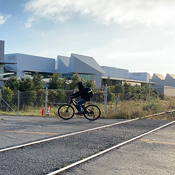 Cyclist-crosses-railroad-tracks-on-Chilco-Street-with-Facebook-building-in-the-background
