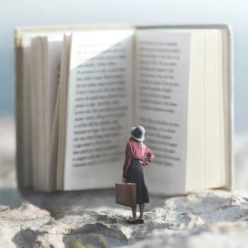 Tiny human figure standing between pages of huge open book