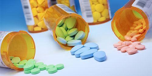 Blog--prescription-medication-spilling-out-of-open-bottles